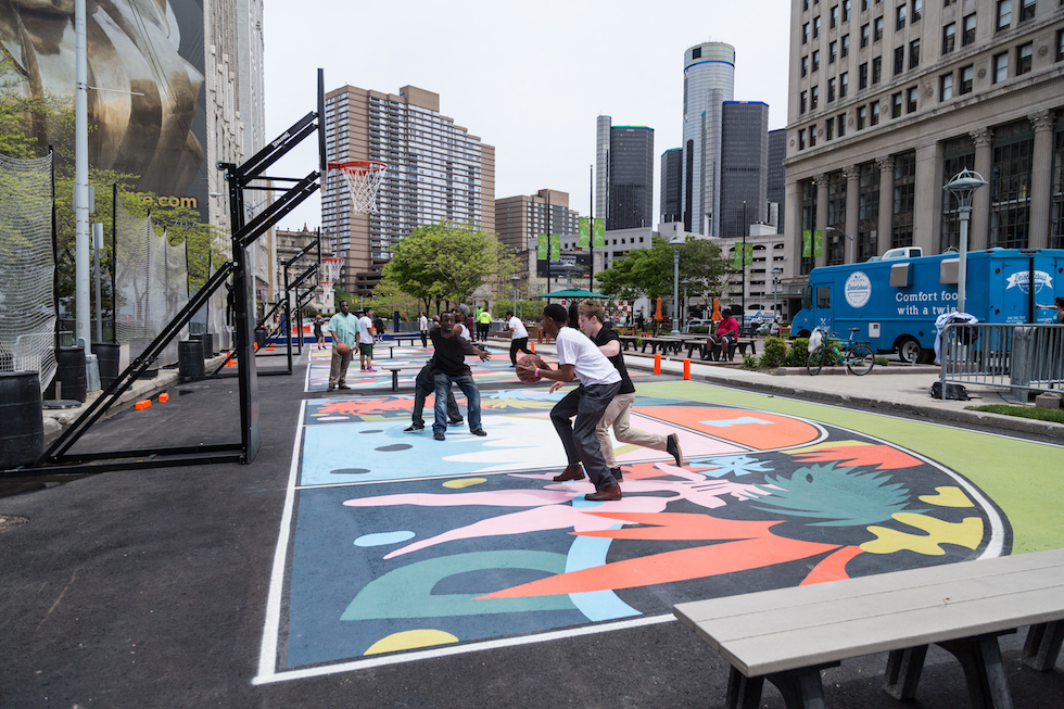 Visitors enjoy the basketball court in the Quicken Loans Sports Zone at Cadillac Square Park. The court features designs by local artist Jesse Kassel.