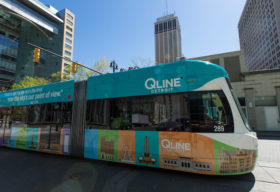 The QLine with it's new wrap prior to opening, May 2017. The light rail traveling on Woodward Avenue past Campus Martius.