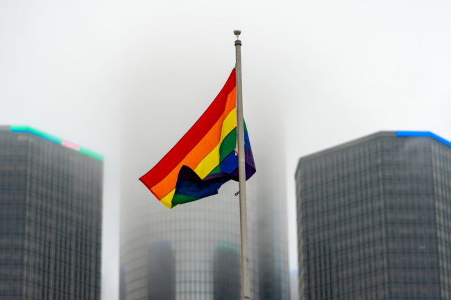 Pride Flag With Ren Cen In Background On Cloudy Day